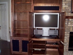 The TV hides behind pocket doors. Note the provision for media storage, equipment and speakers.  The seperate location for the center channel speaker allows CD's to be heard without opening the TV doors.