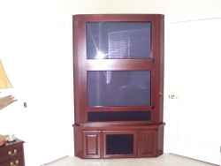 This Cherry corner unit is on casters and is home to a pair of Plasma TVs and equipment.